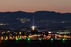 Atterraggio di aeroplano all'aeroporto al crepuscolo Fotografie Stock Libere da Diritti