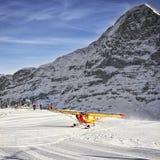 Atterraggio di aeroplano giallo alla località di soggiorno alpina in alpi svizzere nel winte Fotografia Stock Libera da Diritti