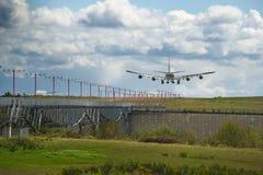 Atterraggio di aeroplano pesante del carico sulla pista con verde fertile e cielo blu immagini stock