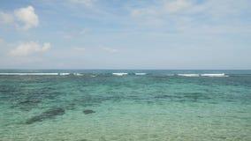 Atterraggio di aeroplano sull'aeroporto di Bali dell'isola sotto il mare blu con le onde sull'orizzonte archivi video