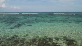 Atterraggio di aeroplano sull'aeroporto di Bali dell'isola sotto il mare blu con le onde sull'orizzonte stock footage