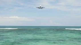 Atterraggio di aeroplano sull'aeroporto di Bali dell'isola sotto il mare blu con le onde sull'orizzonte video d archivio