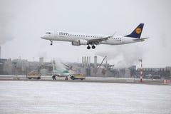 Atterraggio di Lufthansa CityLine Embraer ERJ-195 D-AEMD nell'aeroporto di Monaco di Baviera Immagini Stock Libere da Diritti