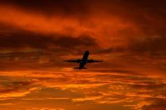 Atterraggio o decollo di aeroplano nel tramonto con il cielo rosso nell'aeroporto internazionale di Bucarest, macchia normale fotografia stock libera da diritti