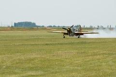 Atterraggio piano dello show aereo sul campo di erba Fotografia Stock