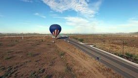 Atterrissage chaud aérien de ballon à air par la route à grand trafic dans le désert banque de vidéos