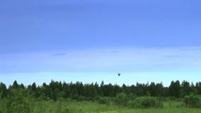 Atterrissage chaud de ballon à air dans la temps-faute de ciel bleu banque de vidéos