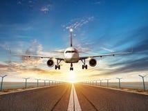 Atterrissage d'avion à la piste d'aéroport dans la lumière de coucher du soleil Images stock