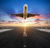 Atterrissage d'avion à la piste d'aéroport dans la lumière de coucher du soleil Images libres de droits
