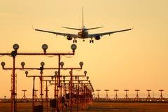 Atterrissage d'avion à réaction de coucher du soleil de YVR, Vancouver Photographie stock
