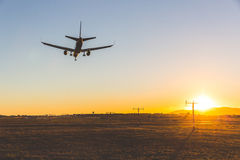 Atterrissage d'avion au coucher du soleil, vue inférieure Photos libres de droits