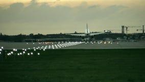 Atterrissage d'avion commercial de moteur jumeau à l'aéroport le soir, vue arrière Photos libres de droits