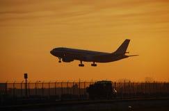 Atterrissage d'avion de ligne à réaction à l'aube Photos stock