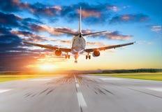 Atterrissage d'avion de passager au coucher du soleil sur une piste photos libres de droits