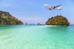 Atterrissage d'avion de passager au-dessus de petite île en mer bleue Image libre de droits