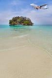 Atterrissage d'avion de passager au-dessus de petite île en mer bleue Photographie stock