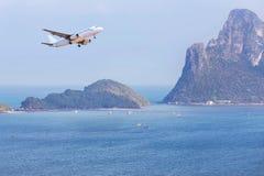 Atterrissage d'avion de passager au-dessus de petite île en mer bleue et plage tropicale Images stock
