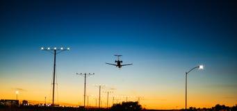Atterrissage d'avion pendant l'aube juste avant le lever de soleil Images stock