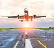 Atterrissage d'avion sur la piste à l'aéroport à l'aube de coucher du soleil Images stock
