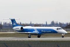 Atterrissage d'avions de Dniproavia Embraer ERJ-145 sur la piste Images stock