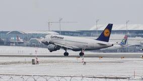 Atterrissage de Lufthansa Airbus A319-100 D-AILT dans l'aéroport de Munich, dans la neige banque de vidéos