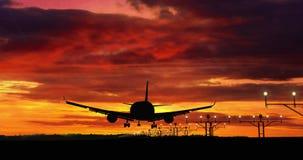 Atterrissage de silhouette d'avion sur le fond rouge de ciel banque de vidéos