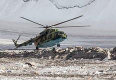 Atterrissage militaire d'hélicoptère sur la glace du glacier de montagne Images stock