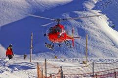Atterrissage rouge d'hélicoptère à la station de sports d'hiver suisse près du mountai de Jungfrau Photo libre de droits