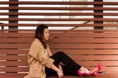 Attesa asiatica di seduta della ragazza Fotografie Stock