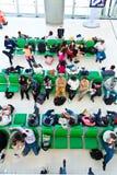 Attesa della gente sui banchi per Fotografia Stock