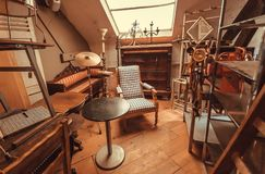Attic of antique store with vintage armchair, decoration, wooden furniture, retro details royalty free stock image