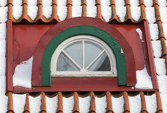 Attic arch window with snow on red tile roof Stock Photos