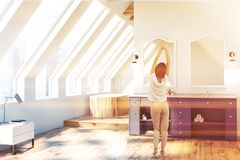 Attic bathroom, blue double sink and tub, woman. Woman in attic bathroom interior with white walls, wooden floor and white double sink standing on blue stock photography