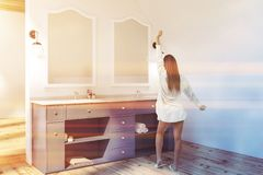Attic bathroom corner, blue double sink, woman. Woman in attic bathroom corner with white walls, wooden floor and white double sink standing on blue countertop stock photo