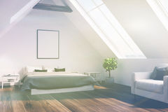 Attic bedroom with a gray bed, poster, side toned Royalty Free Stock Photos