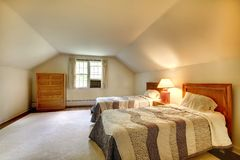 Attic bedroom with simple furniture and vaulted ceiling. Stock Photography