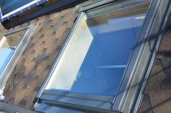 Attic skylight roof windows on the asphalt shingles house roof. Royalty Free Stock Photography