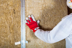 Attic loft insulation by hand. At home Royalty Free Stock Photo
