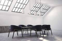 Attic meeting room corner, black chairs. Attic white brick meeting room corner with a concrete floor and dark blue armchairs near a boardroom table. Ceiling Royalty Free Stock Images
