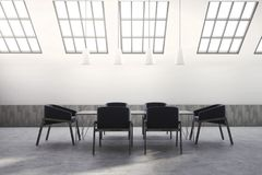 Attic meeting room interior, black chairs. Attic white brick meeting room interior with a concrete floor and dark blue armchairs near a boardroom table. Ceiling Royalty Free Stock Images