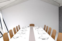 Attic meeting room, white ceiling. Attic conference room interior with a long table, rows of beige chairs near it, glasses of water and clipboards on the table Royalty Free Stock Photography