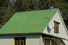 Attic of the house with windows and a roof under the green slate on the background of pines and sky. Attic of a private house with windows and a roof under a royalty free stock image