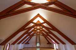 Attic roof beams. Attic with windows, wooden floor and brown roof beams visible stock photo