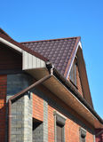 Attic roof with rain gutter and downspout pipe. Royalty Free Stock Photo