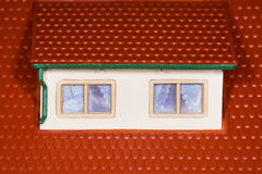 Attic on roof of toy plastic house,two windows Royalty Free Stock Photography