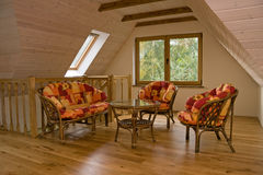 Attic room. With garden furniture. Walls covered with timber planks, beams in the ceiling Stock Photos