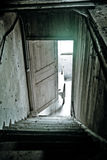 Attic stairs. Stairs and door inside an abandoned house Royalty Free Stock Images