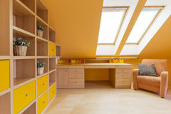 Attic study room idea. New design attic room in orange with wall shelving unit, desk and armchair royalty free stock image
