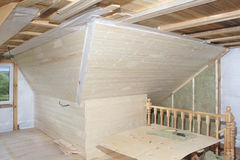 Attic under construction: mounting mineral cotton and deal board Royalty Free Stock Photos