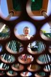 Attimo sorridente del bambino che esamina attraverso i cerchi in piattaforma il campo da giuoco fotografia stock